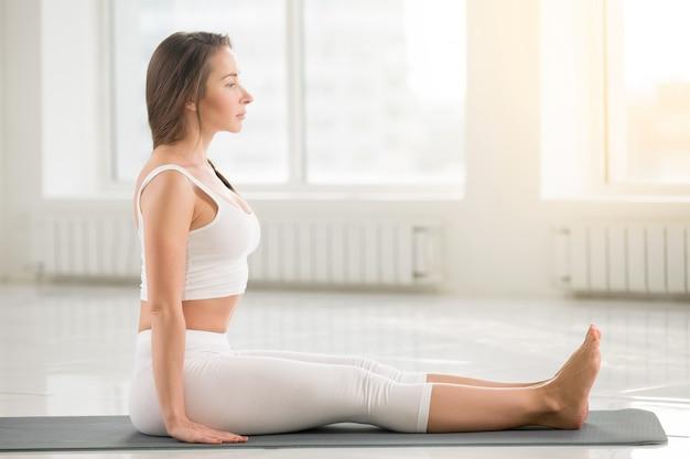 Jovem, mulher atraente sentada em pose dandasana, ba branca