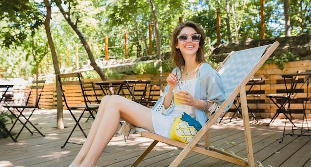 Jovem mulher atraente sentada em uma espreguiçadeira com roupa de moda de verão, estilo hippie, vestido branco, capa azul, óculos de sol, bebendo limonada, acessórios elegantes, relaxante, pernas longas e magras em sandálias