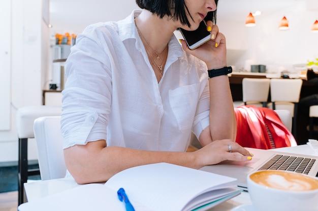 Jovem mulher atraente sentada no escritório coworking e digitando em seu computador laptop teclado e fazendo anotações de manhã. mesa com telefone, notebook, copos e uma xícara de café. conceito de negócios