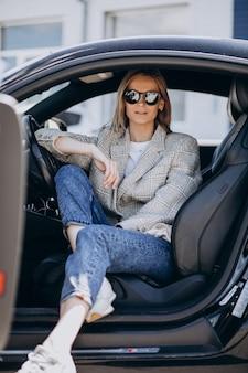 Jovem mulher atraente, sentado em um carro