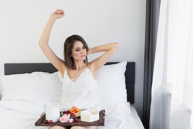 Jovem mulher atraente, sentado na cama com café da manhã