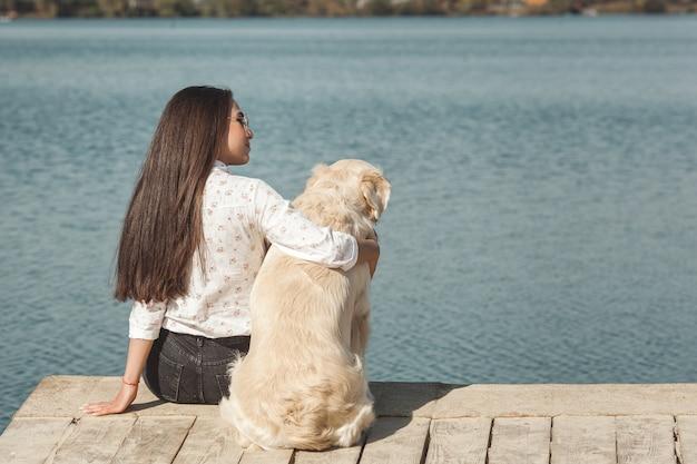Jovem mulher atraente, sentado no píer com seu cachorro. melhores amigos ao ar livre
