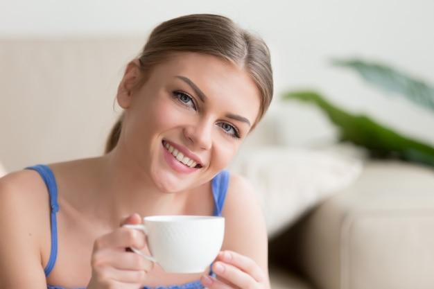 Jovem mulher atraente sorridente desfrutando de café olhando para a câmera