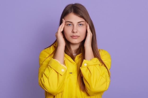 Jovem mulher atraente tem estresse e dor de cabeça, mantendo os dedos nos templos com expressão triste, posando isolado sobre parede lilás.