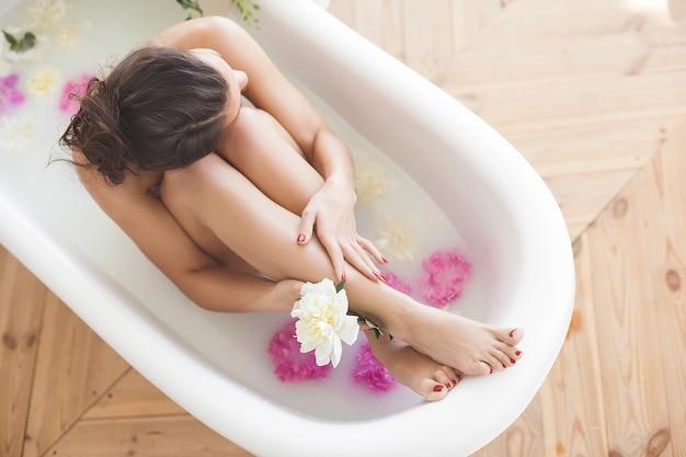 Jovem mulher atraente tomando banho com leite e flores