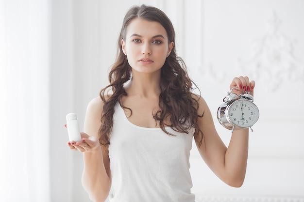 Jovem mulher atraente tomando pílulas na hora certa