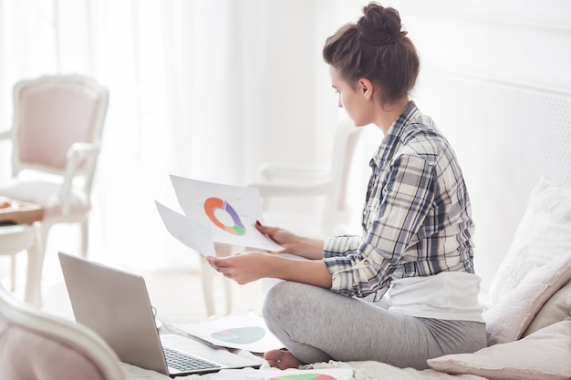 Jovem mulher atraente, trabalhando em casa no laptop