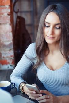 Jovem mulher atraente trabalhando em um café e bebendo café