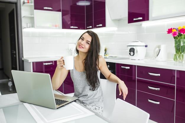 Jovem mulher atraente trabalhando no pc na cozinha. mulher trabalhando no computador de manhã. freelancer no laptop interno.