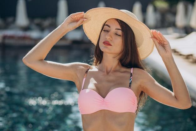 Jovem mulher atraente usando chapéu e em pé à beira da piscina