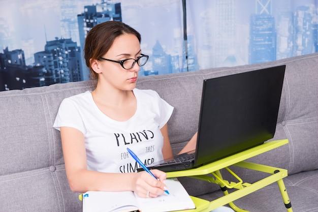 Jovem mulher atraente usando óculos, trabalhando em um laptop, fazendo seus negócios em casa, segurando uma caneta enquanto lê as informações na tela