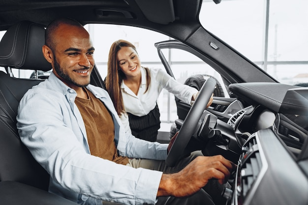 Jovem mulher atraente, vendedora em showroom de carros, mostrando um carro para o cliente