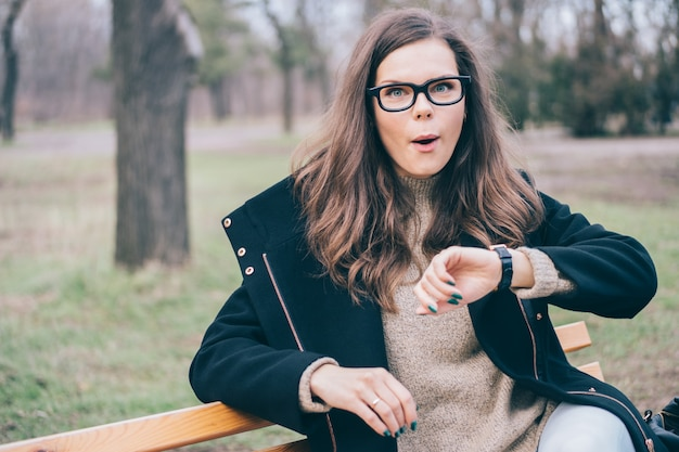 Jovem mulher atraente verifica o tempo em um relógio de pulso