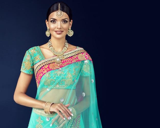 Jovem mulher atraente vestida com um tradicional terno indiano sari com blusa verde e xale