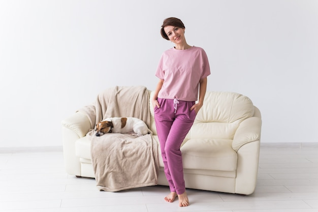 Jovem mulher atraente vestida de pijama colorido lindo posando com cachorro como modelo em sua sala de estar. pijamas confortáveis, relaxamento em casa e o conceito de moda feminina.