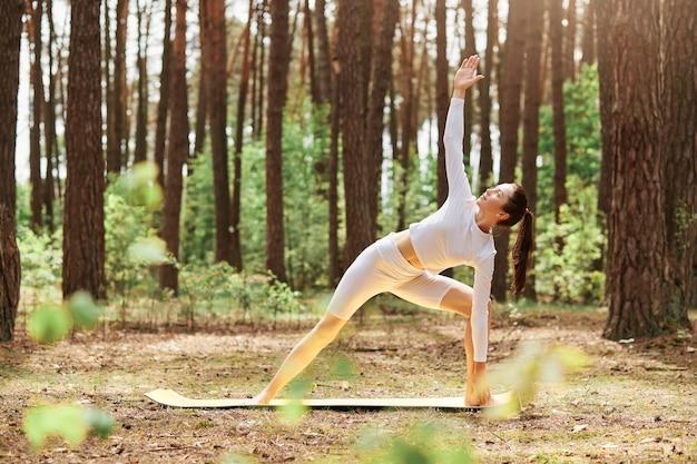 Jovem mulher atraente vestindo roupa esportiva branca, fazendo prática de ioga na bela natureza na floresta, jovem mulher adulta com corpo perfeito em pose de triângulo.