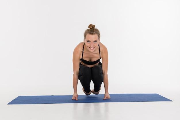 Jovem mulher atrativa desportiva que faz a prática da ioga no fundo branco. corvo - bakasana.
