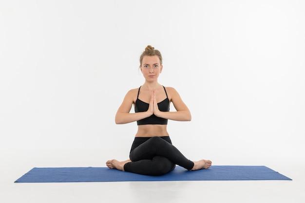 Jovem mulher atrativa desportiva que faz a prática da ioga no fundo branco. gomukhasana