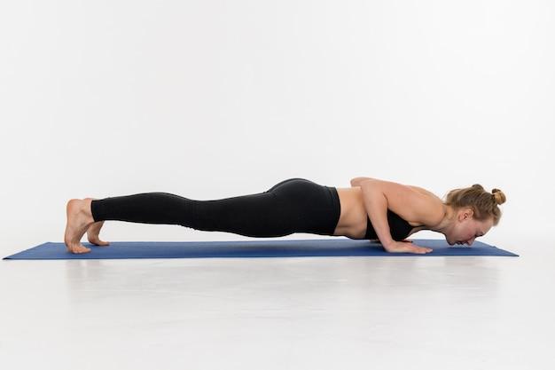 Jovem mulher atrativa desportiva que faz a prática da ioga no fundo branco. quatro funcionários com membros - chaturanga.