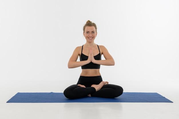 Jovem mulher atrativa desportiva que faz a prática da ioga no fundo branco. sukhasana.
