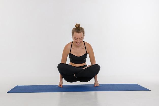 Jovem mulher atrativa desportiva que faz a prática da ioga no fundo branco.
