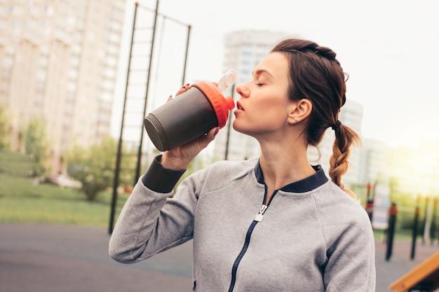 Jovem mulher atrativa do ajuste na água da bebida do desgaste do esporte e no resto na área do exercício da rua.