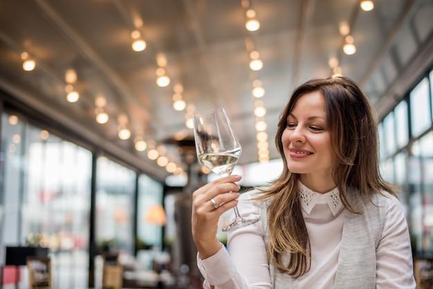 Jovem mulher atrativa no restaurante do café que prova o vinho.