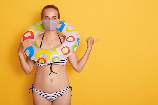 Jovem mulher atrativa no roupa de banho com anel de borracha na máscara médica isolada sobre a parede amarela, apontando de lado com o polegar, espaço da cópia para a propaganda.