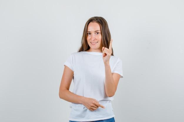 Jovem mulher avisando alguém com gesto de dedo em t-shirt branca, vista frontal de shorts.