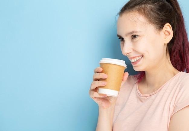 Jovem mulher bebe café de copo de papel e sorri sobre fundo azul