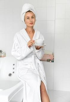 Jovem mulher bebe café no banheiro. rotina de cuidados com a pele. vida lenta, pare de correr, aproveitando o conceito de vida