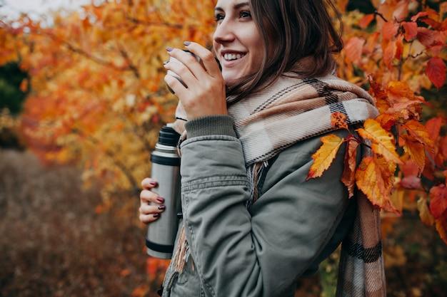 Jovem mulher bebe chá na floresta de outono