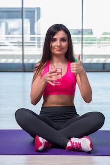Jovem mulher bebendo água fresca no conceito de saúde