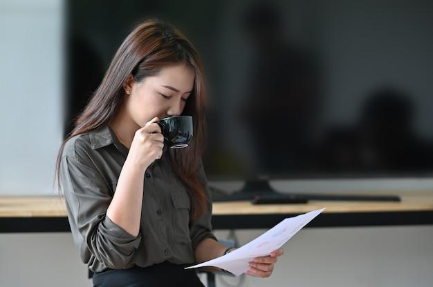 Jovem mulher bebendo café e papel financeiro de análise.