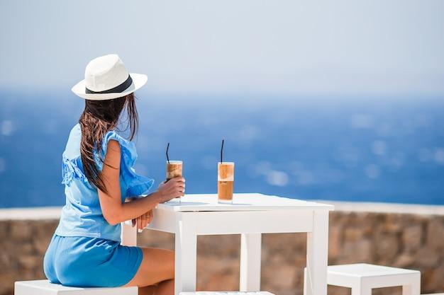 Jovem mulher bebendo café frio, apreciando a vista para o mar