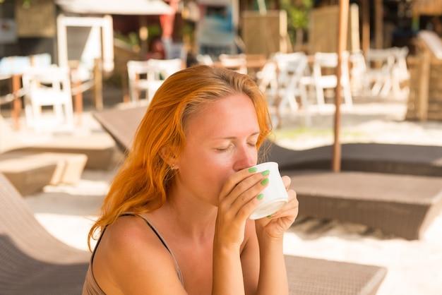 Jovem, mulher, bebendo café na praia