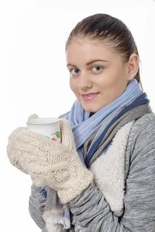 Jovem mulher bebendo chá com luvas para aquecer