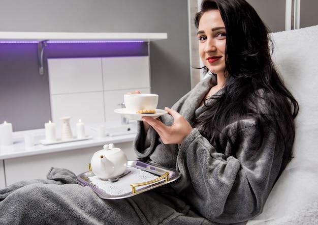 Jovem mulher bebendo chá de ervas após procedimentos de spa.