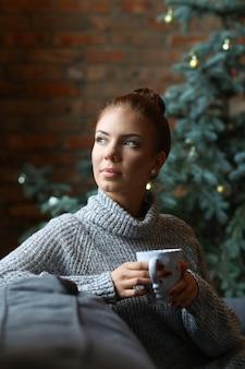 Jovem mulher bebendo chá quente no sofá