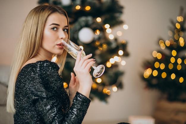 Jovem mulher bebendo champanhe perto da árvore de natal