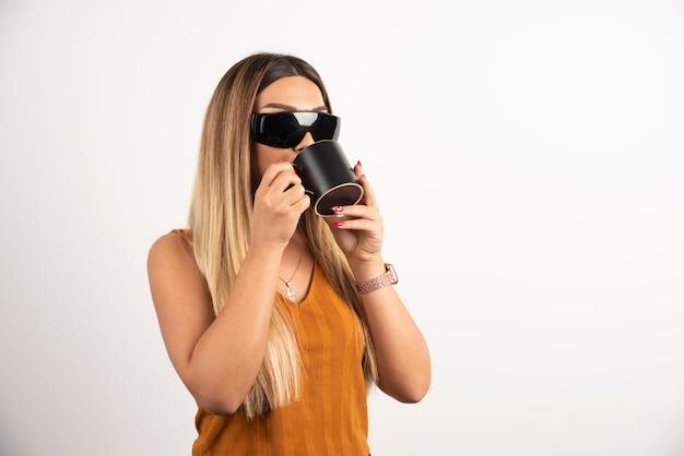 Jovem mulher bebendo do copo preto e usando óculos de proteção.