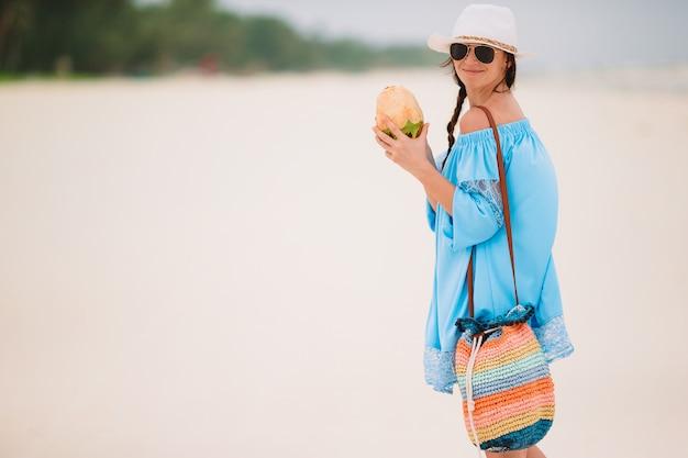 Jovem mulher bebendo leite de coco durante férias tropicais