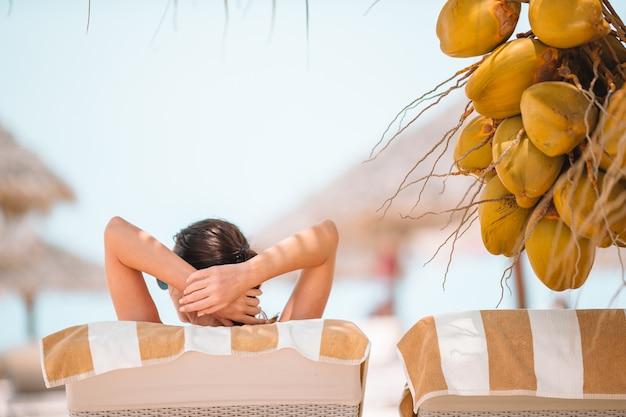 Jovem mulher bebendo leite de coco em um dia quente na praia.