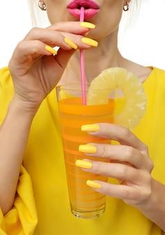 Jovem mulher bebendo suco de abacaxi com alegria. manicure moderna com esmalte amarelo em um formulário longo.