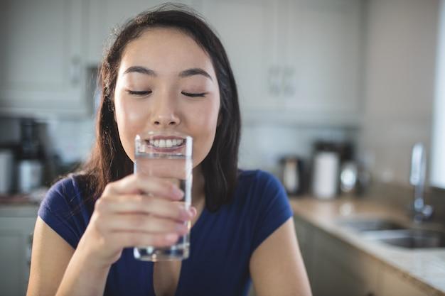Jovem mulher bebendo um copo de água na cozinha