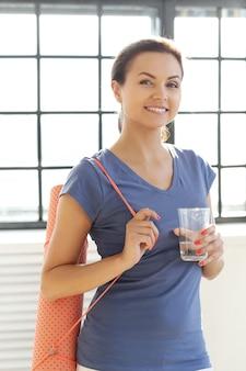 Jovem mulher bebendo um copo de água