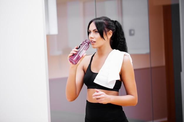 Jovem mulher beber água limpa no ginásio de fitness