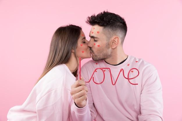 Jovem mulher beijando homem com corações de papel no rosto e sinal de amor