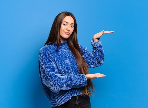 Jovem mulher bem casual segurando um objeto com as duas mãos no espaço lateral de cópia, mostrando, oferecendo ou anunciando um objeto