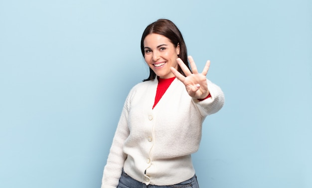 Jovem mulher bem casual sorrindo e parecendo amigável, mostrando o número quatro ou o quarto com a mão para a frente, em contagem regressiva